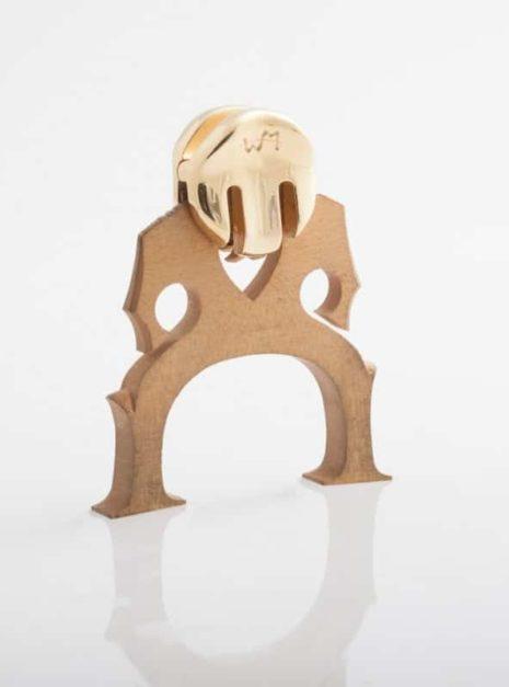 La sourdine d'entraînement WMutes pour violoncelle dorée installée sur le chevalet